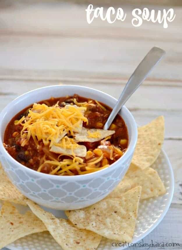 bowl of taco soup topped with chips and shredded cheese