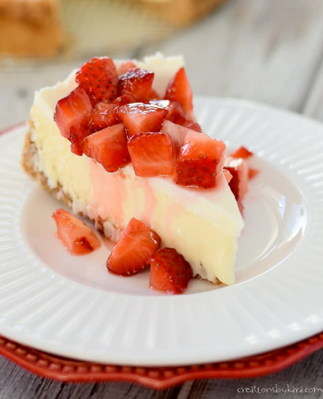 cheesecake with sour cream topping, topped with fresh strawberries