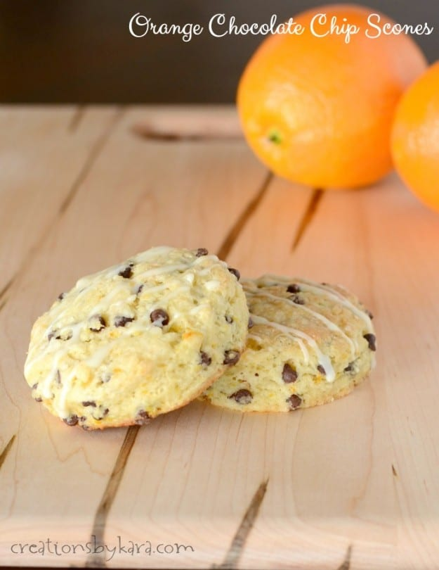 chocolate chip scones on a cutting board with oranges