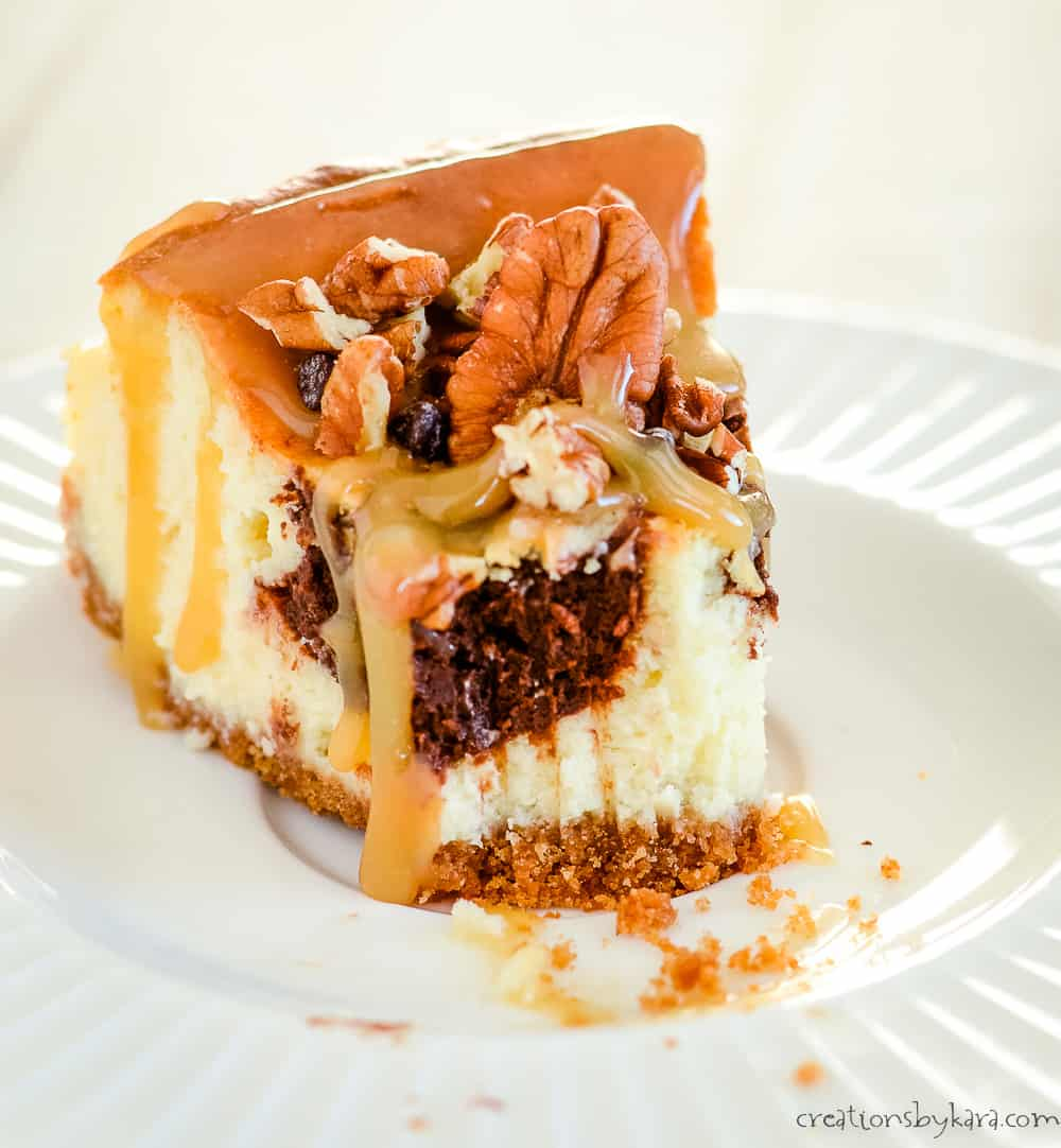 caramel turtle cheesecake on a plate with a bite taken out of it