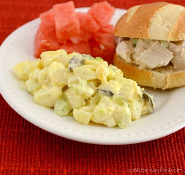 plate of potato salad, watermelon, and chicken salad sandwich