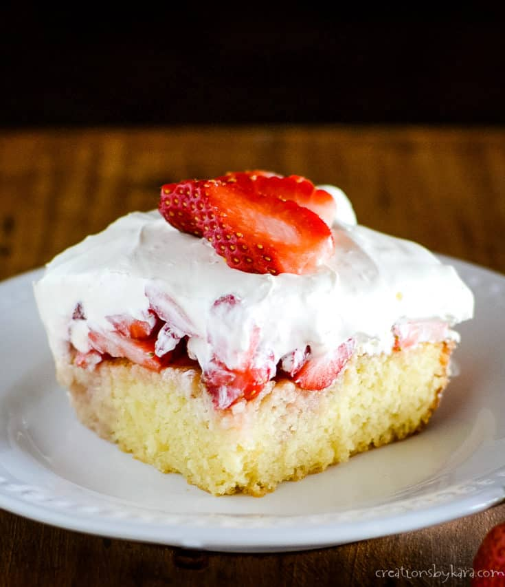 plate of yellow cake with strawberries and cream topping