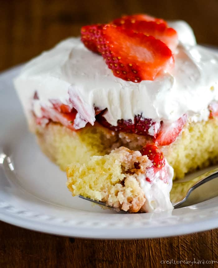 bite of cake with cream and strawberries
