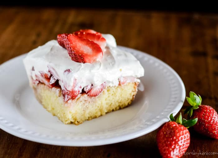cake with sweetened condensed milk topping and fresh strawberries