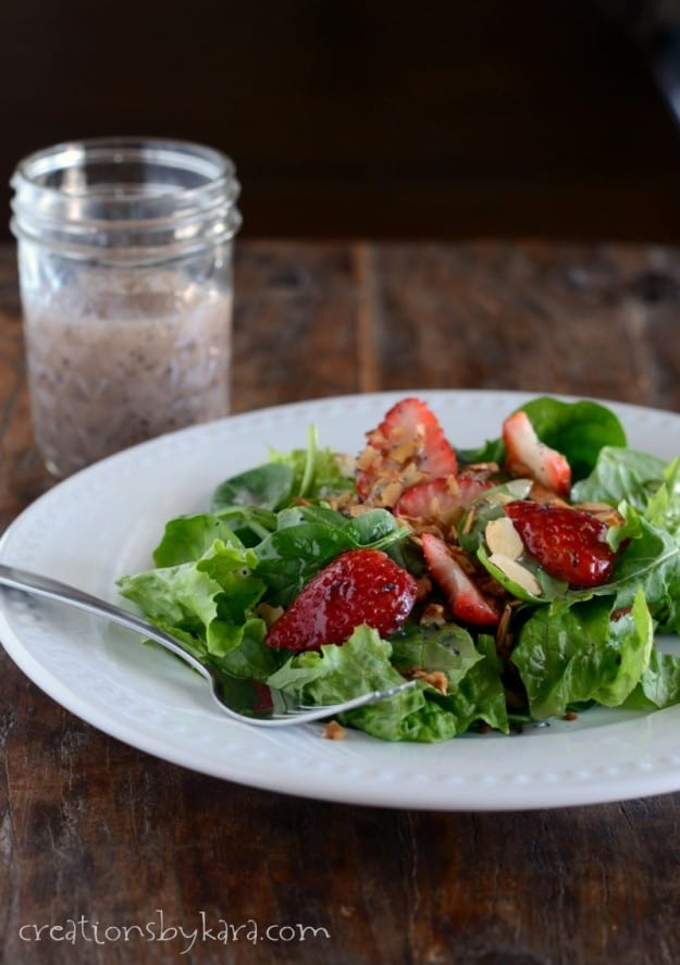 plate of salad with raspberry poppy seed dressing in the background