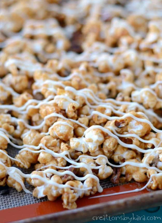 Cinnamon Roll Caramel Popcorn - popcorn covered in cinnamon caramel sauce, then drizzled with white chocolate. A festive caramel popcorn recipe that everyone loves!
