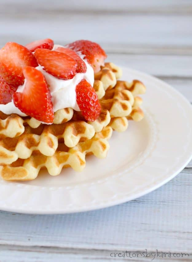 plate of waffles with whipped cream and strawberries