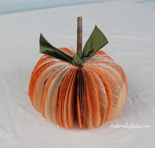 Book page pumpkin made from old book with wood stem and green ribbon