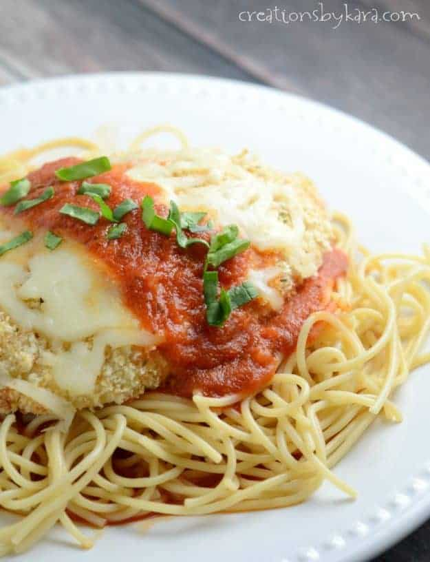 plate of pasta topped with chicken parmesan
