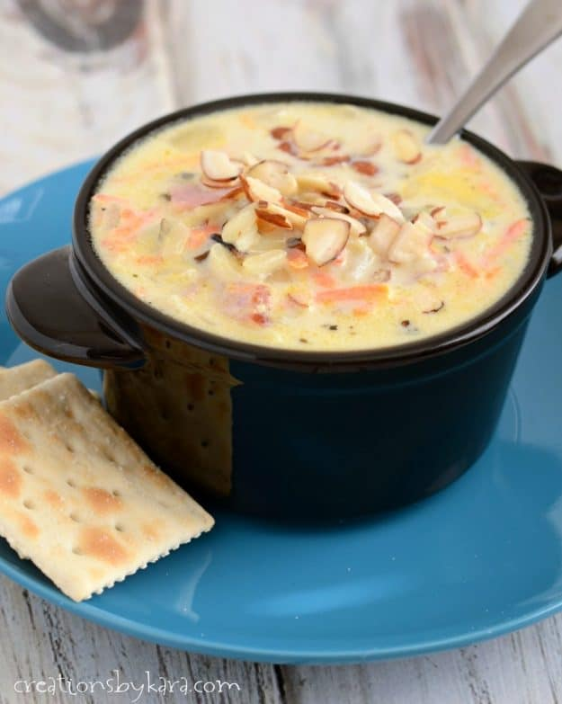 close up of bowl of wild rice ham soup with saltine crackers on the side