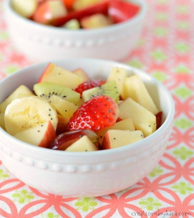 close up of bowl of fruit with honey lime dressing