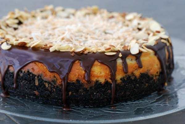 close up of coconut almond cheesecake with chocolate ganache dripping down the sides