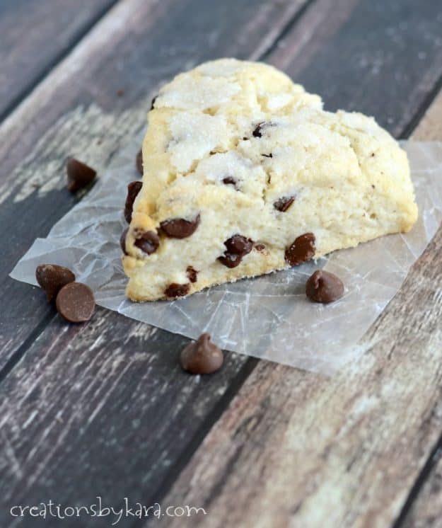 close up of chocolate chip scone on waxed paper with extra chocolate chips