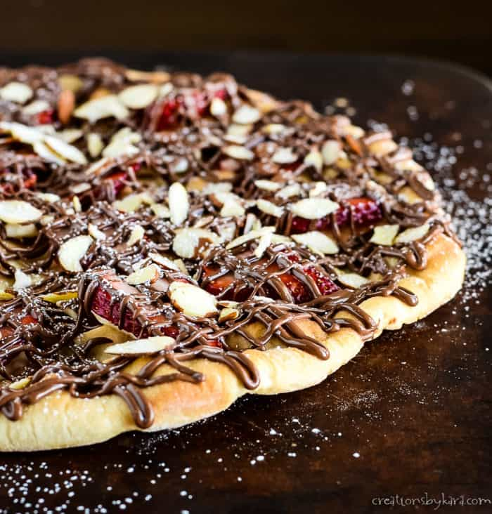 dessert pizza with sliced strawberries and nutella