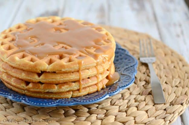 waffles with peanut butter syrup on a blue plate with a fork on the side