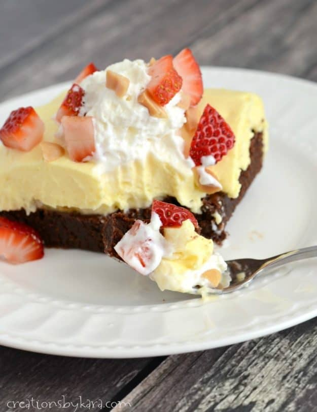 bite of brownie topped with bananas, pudding, strawberries, cream, and nuts