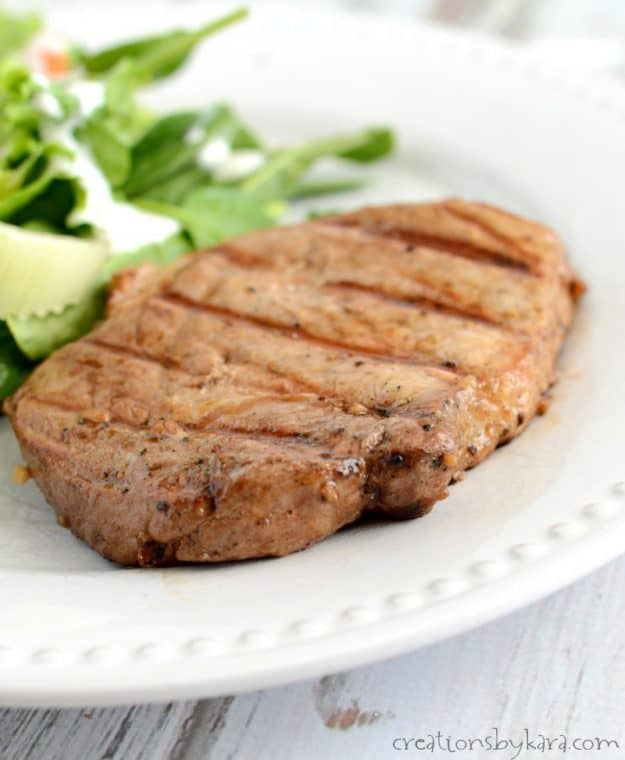 plate with a grilled pork chop and salad