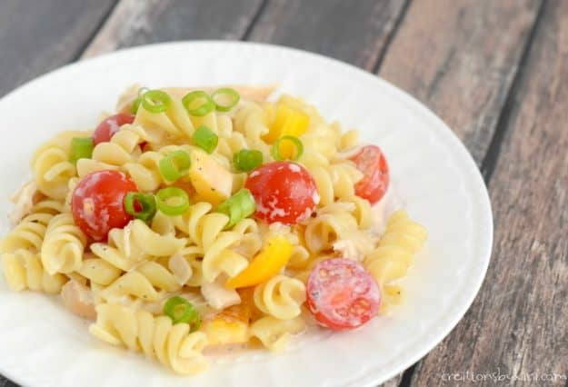 plate of pasta topped with tomatoes and green onions