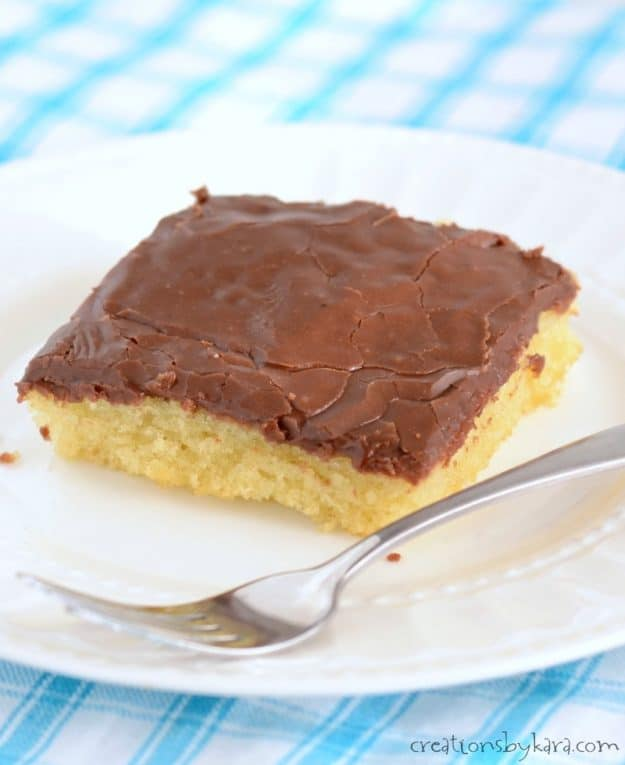 slice of hot yellow sheet cake with chocolate frosting on a plate with a fork