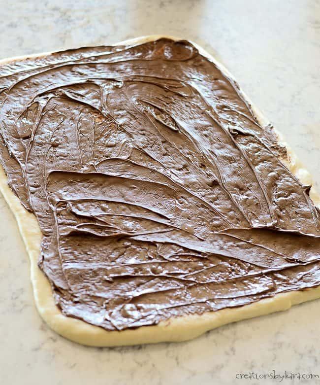 Spread nutella on dough for nutella rolls