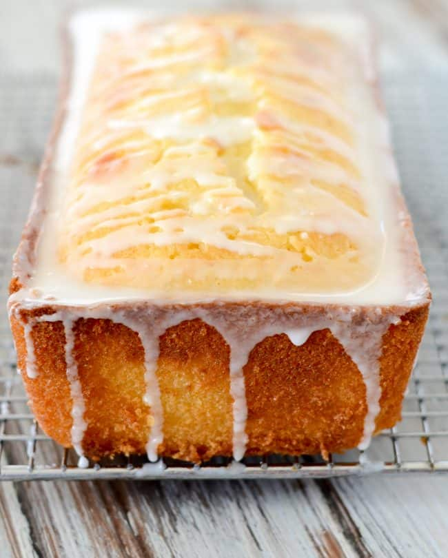 loaf of lemon pound cake on a cooling rack with lemon glaze dripping down
