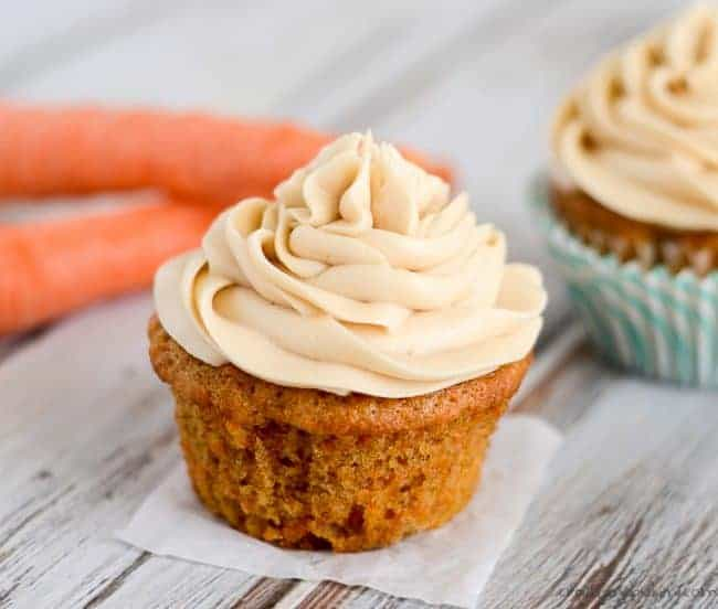 Unwrapped carrot cake cupcake with swirled brown sugar cream cheese frosting on parchment paper