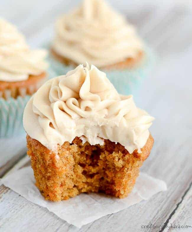 Carrot cake cupcake with a bite taken out of it.