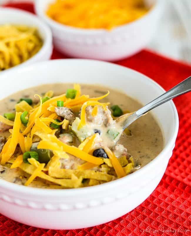 close up of a bowl of nacho soup with a spoon