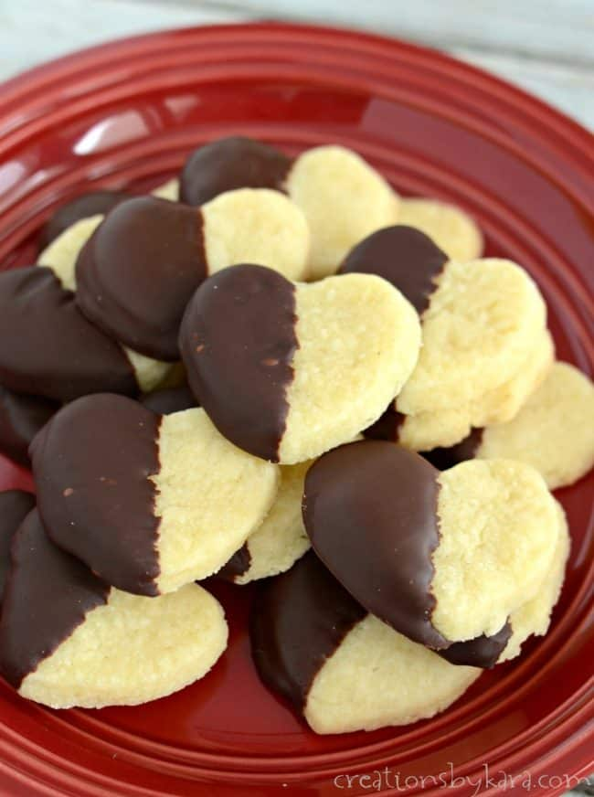 stack of chocolate dipped shortbread hearts on a red plate