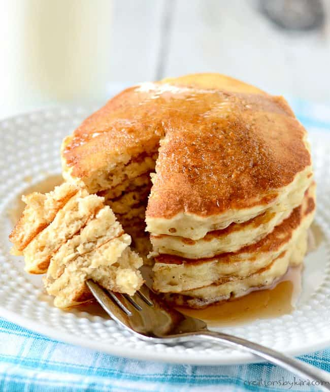 stack of oatmeal pancakes and syrup on a plate with a fork