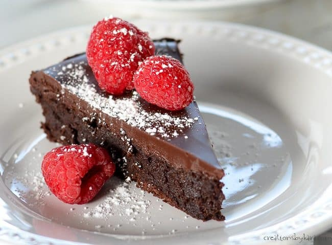flourless chocolate cake with chocolate ganache glaze on a plate with raspberries