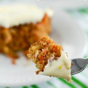 carrot cake with orange cream cheese frosting on a fork