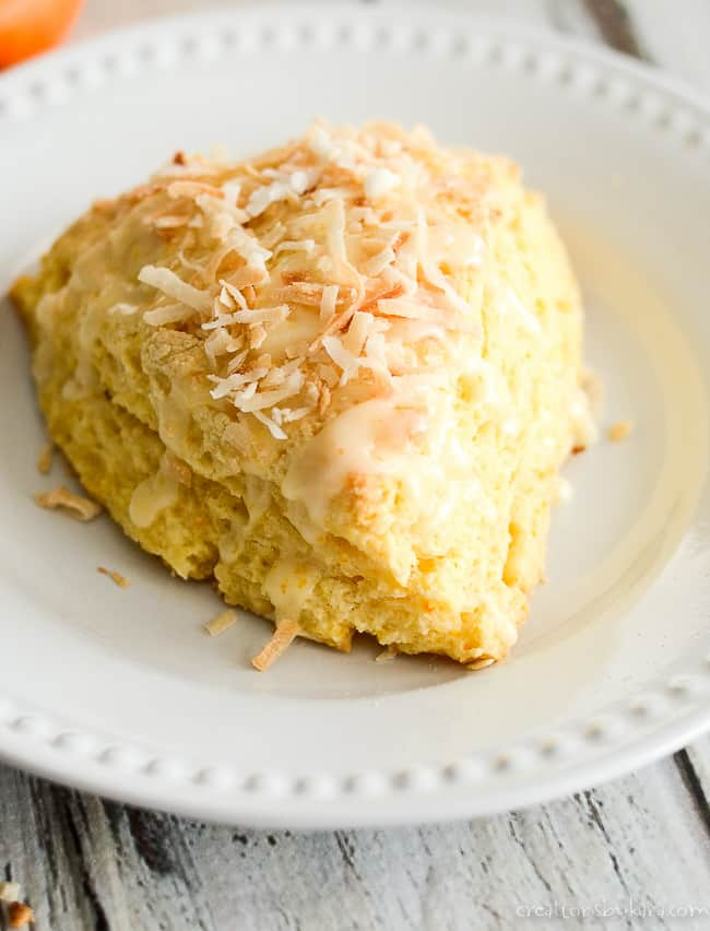 close up of coconut orange scones on a white plate