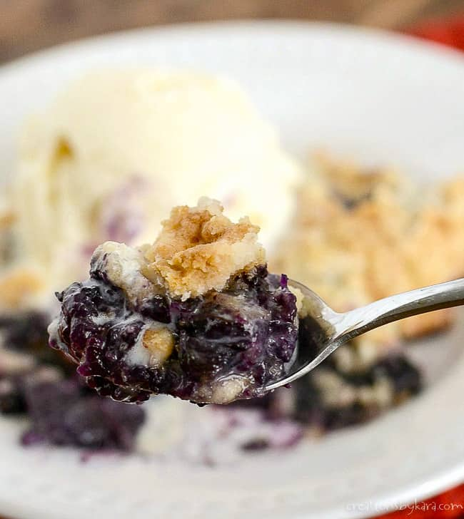 close up of spoonful of blueberry dump cake