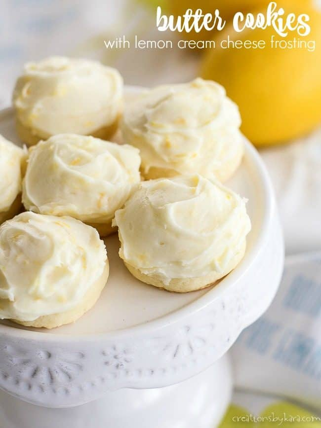 butter cookies with lemon cream cheese frosting on a white cake stand