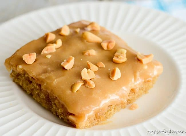 close up of piece of peanut butter sheet cake on a white plate