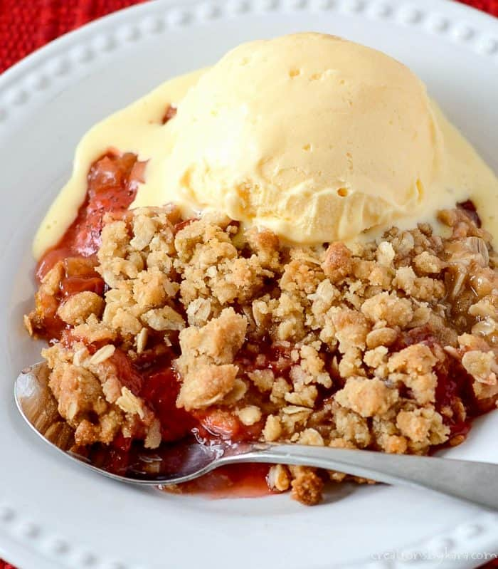close up of warm strawberry rhubarb crisp with vanilla ice cream