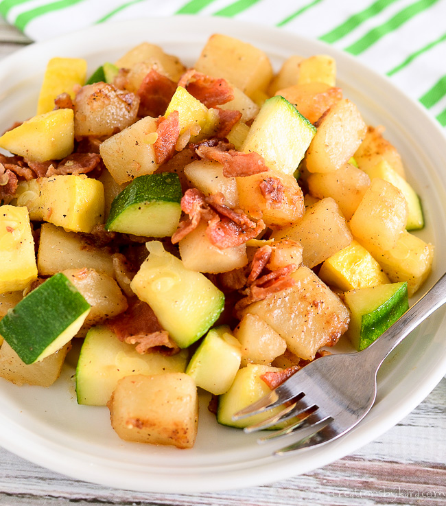 sauteed zucchini, potatoes, and bacon on a plate with a fork