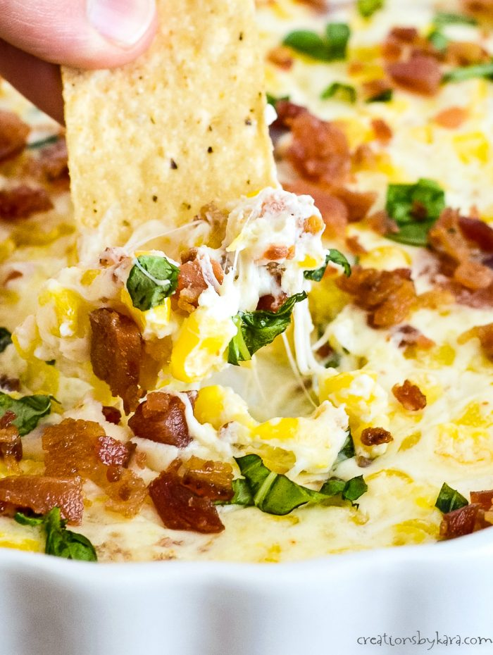 close up of creamy corn dip with bacon and basil
