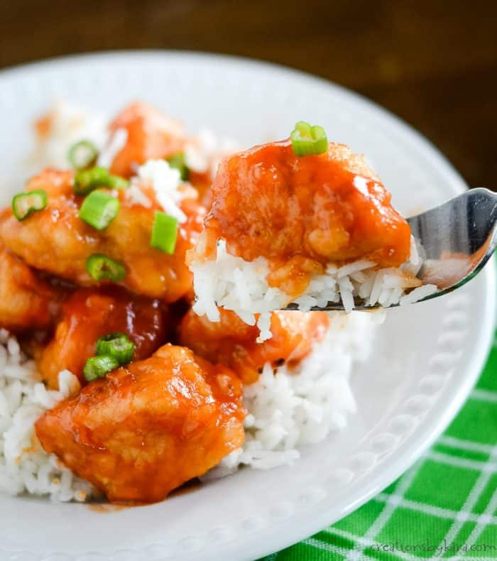 forkful of rice and chicken with sweet and sour sauce