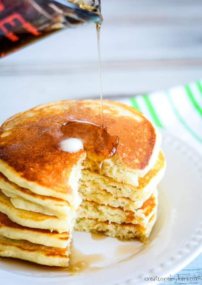 syrup being poured over a stack of pancakes