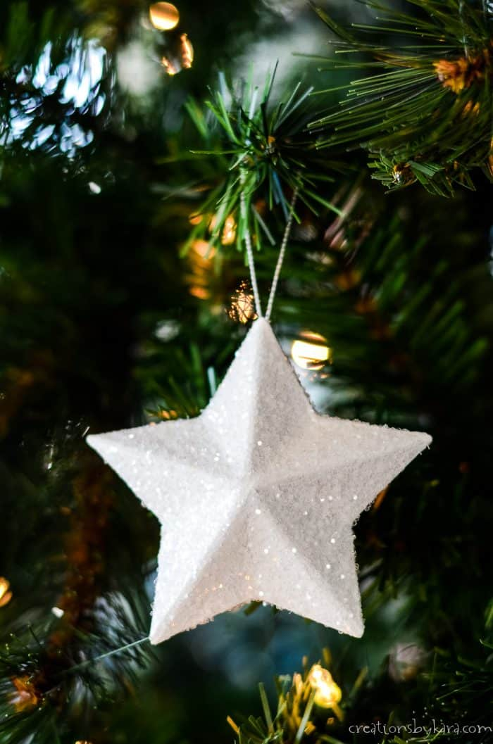 white sparkling star tree ornament hanging on a branch