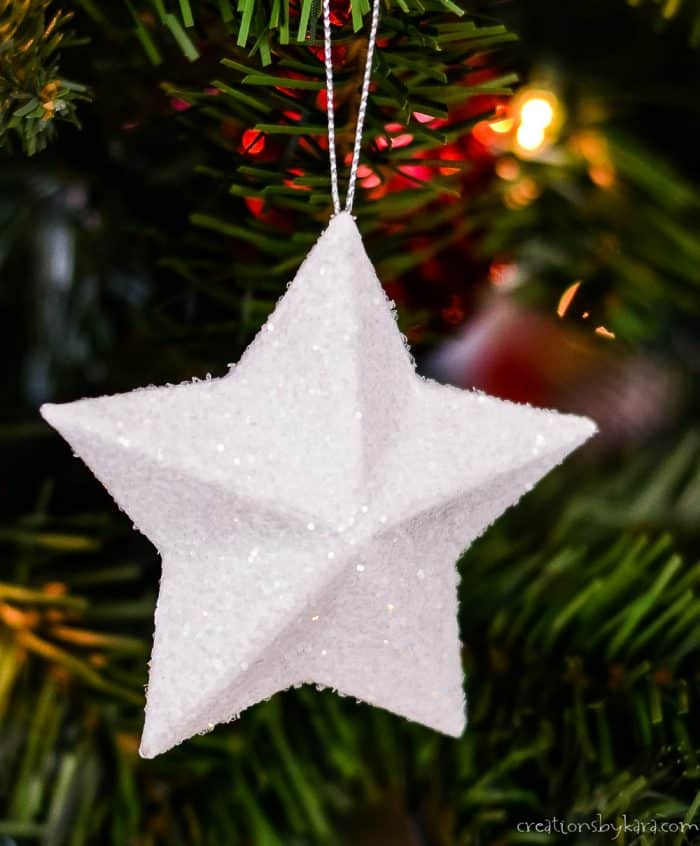 white glitter star hanging on Christmas tree