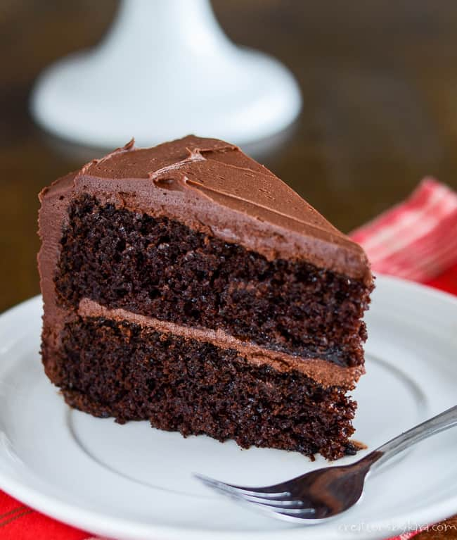 slice of two layer cake with chocolate frosting on a plate with a fork