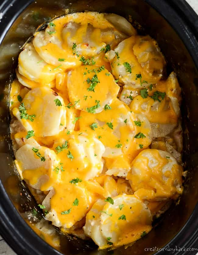 scalloped potatoes in a crock pot topped with melted cheese