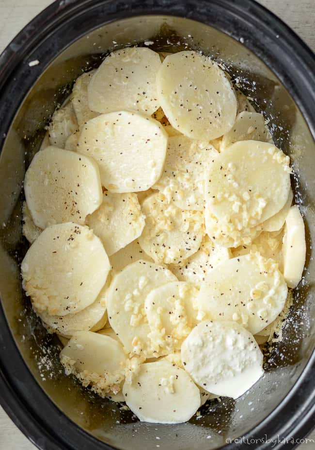 crockpot layered with sliced potatoes, cream, and seasonings