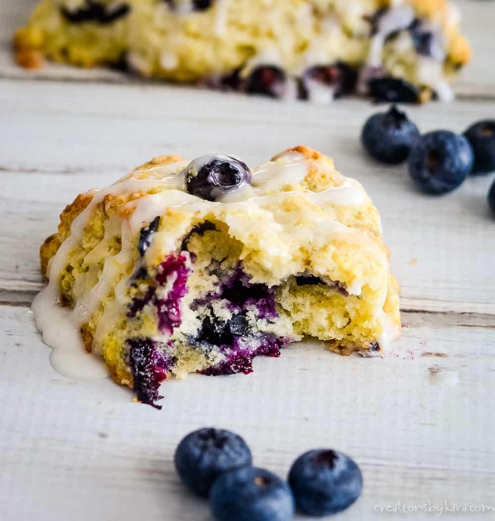 glazed lemon blueberry scone broken in half surrounded by blueberries