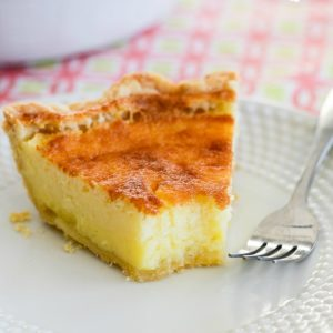 slice of buttermilk pie on a white plate with a fork