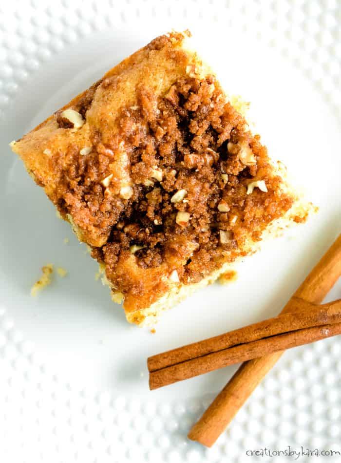 slice of cinnamon coffee cake on a plate with cinnamon sticks