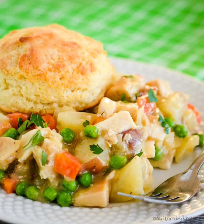 plate of crock pot chicken pot pie topped with a biscuit